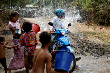Children splash a motorbike driver with water during Thingyan festival celebrations to commemorate the Burmese New Year in Pyay