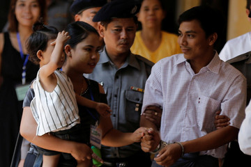 Detained Reuters journalist Kyaw Soe Oo greets his family while arrives to a court hearing in Yangon