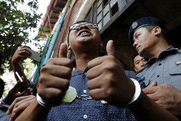 Detained Reuters journalist Wa Lone talks to media while is escorted by police after a court hearing in Yangon