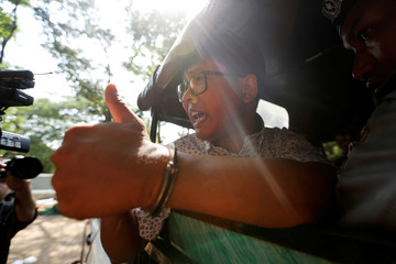 Detained Reuters journalist Wa Lone is transported in a police vehicle after a court hearing in Yangon