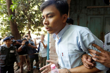 Detained Reuters journalist Kyaw Soe Oo is escorted by police before a court hearing in Yangon