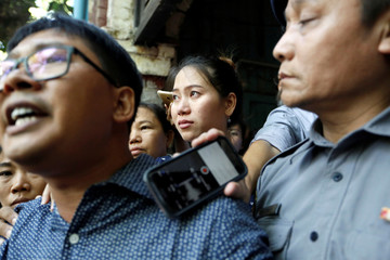 Pan Ei Mon, wife of detained Reuters journalist Wa Lone listens to himn while talks to media after a court hearing in Yangon