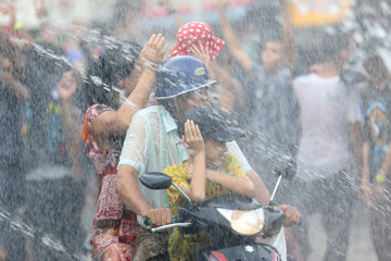 A family on a motorbike are splashed with water during Thingyan festival celebrations to commemorate the Burmese New Year in Pyay