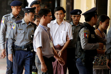 Detained Reuters journalist Kyaw Soe Oo is escorted by police before a court hearing in Yangon Myanmar