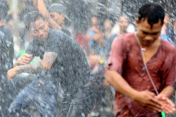 A man dances while people splash water during Thingyan festival celebrations to commemorate the Burmese New Year in Pyay