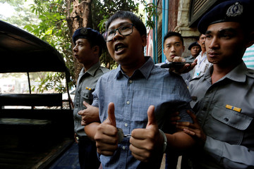Detained Reuters journalist Wa Lone is escorted by police after a court hearing in Yangon