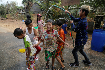 Children play with water during Thingyan festival celebrations to commemorate the Burmese New Year in a village near Pyay