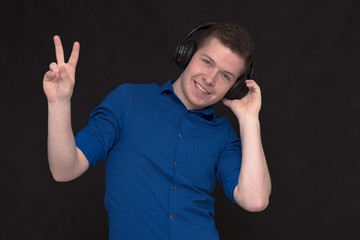 Portrait of a young handsome man on a black background with headphones listening to music.