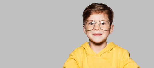 Little attractive boy in yellow jacket and big glasses. Funny child posing, gray wall on background. Close up portrait of smiling boy.