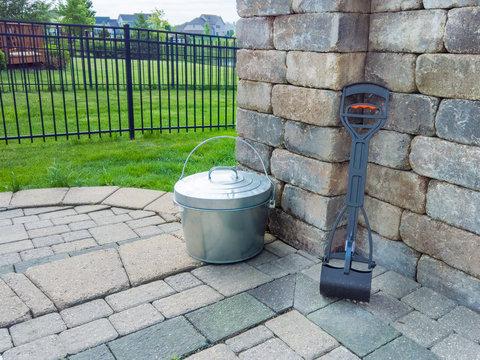 Pooper scooper and metal bucket in a garden