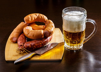 A mug of beer and smoked sausage on the table.