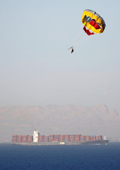 A woman parasails above the water near the Zim Europa container ship crossing the Gulf of Suez towards the Red Sea before entering the Suez Canal, in El Ain El Sokhna in Suez