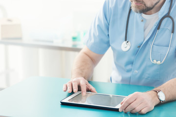 Doctor with stethoscope using tablet