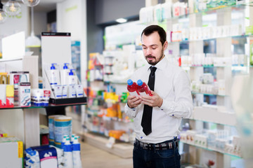 Male client looking assortment in pharmacy
