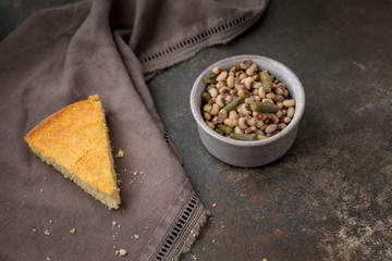 A Slice of Homemade Buttermilk Cornbread with a Bowl of Field Peas and Snap Beans on a Dark Background