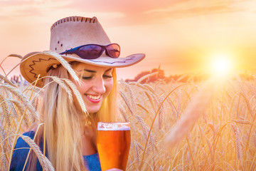 sexy woman in barley holds a glass of beer, sunset