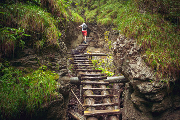 Hiker walking hard way through the canyon in the Tatra Mountains, Slovakia. The abandoned old wooden bridge going in deep wild forest. Outdoor extreme leisure. Travel, sports, nature background