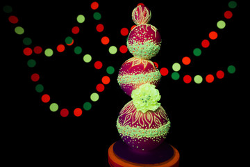 Neon UV photography bright colorful wedding cake glows fluorescent colors on a dark background in the rays of ultraviolet