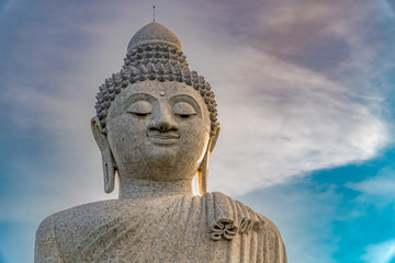 Low angle view of white marble big Buddha statue on top of the hill in evening with blue sky background at Phuket, Thailand.