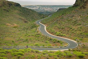 Fahrradfahrer auf einer schlangenförmigen Bergstrasse