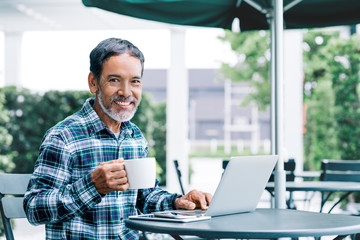 Portrait of happy white stylish short beard mature man drinking coffee while using laptop. Casual urban lifestyle of retired hispanic people, adult asian man sitting, smiling at modern cafe outdoor.