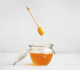 Raw organic honey jar with dipper that floats in the air