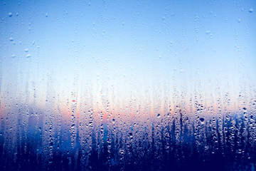 Clear water drops on the surface of the glass window. Color transition .Light blue, white, pink, dark blue shades. Perfect background for the artistic collages and illustrations.