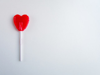 Red heart lollipop on white background with copy space