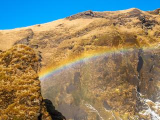 Rainbow over mountain near Skogafoss waterfall in Iceland in winter season