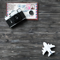 Concept of planning vacation, business travel, voyage, trip, holidays. Time to travel, time to relax. Retro camera, white model of airplane, envelope for travel, compass on aged wooden background.