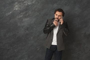 Cheerful bearded man talking on phone