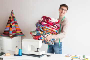 handcraft, creativity, patchwork concept. by the work table with lots of tools for there is a young handsome man with charming smile, he is holding amout of colorful quilts