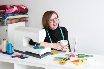 rest, quilt, occupation concept. there is young and charming seamstress with smile, she is taking a break sitting at her work desk with amount of tools for sewing with measuring tape on her shoulders