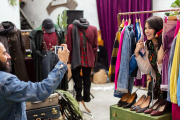 sale, shopping, fashion and people concept - man photographing happy woman by smartphone at vintage clothing store hanger