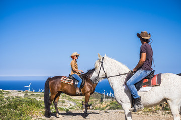 discover nice  places all over the world in alternative way of travel with horses best friends. white caucasian couple in leisure activity outdoor near a windmill farms and under a blue colored sky