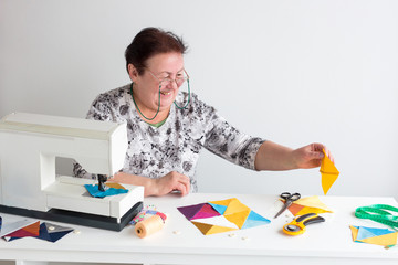 profession, manufacturing, quilting concept. there is old smiling woman in white shirt with floral pattern and glasses, she is sitting at the desk with sewing machine and collecting patches together
