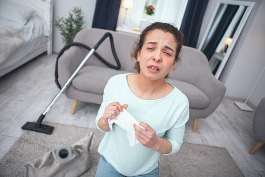 Sneezing hard. Young woman looking desperately sick while inhaling dust coming out of dust container developing allergy to dust