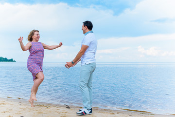 Happy smiling couple, plus size woman at sea outdoors, xl woman on nature, rest and joy the life, man take in hands a lady