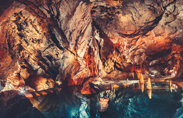 Breathtaking inside view of the grotto in the cave with the crystal clear lake. Fairy tale golden orange and dark blue color combination. The Tatras Mountains, Slovakia.