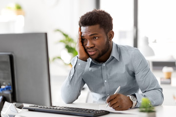 business, people, paperwork and technology concept - stressed african american businessman with computer and papers working at office