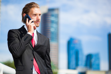 Handsome businessman on the phone outdoor