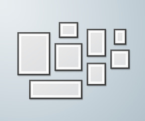 Set of black photo frames of different sizes on the wall. Vector realistic mockup of empty picture frames for design of a gallery for painting and photos. Isolated from the background.