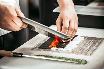 Close-up view of the man s hands cutting the caviar on the seaweed and rice layer. The professionals are making rolls for the tasty sushi in the modern restaurant.