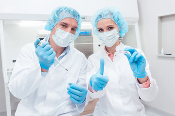 Two scientists with tools posing in the lab looking into camera