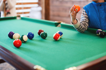balls on a billiard table in a triangle. child playing billiards