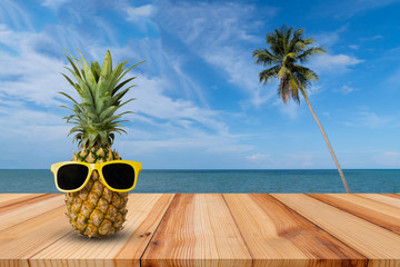 Pineapple on wooden table in a tropical landscape, Fashion hipster pineapple, Bright summer color, Tropical fruit with sunglasses, Creative art concept, Minimal style