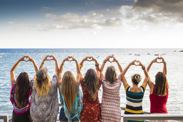 seven girls from the backside doing a heart with the hands looking at the ocean waiting the sunset in vacation leisure activity. friendshipt all together forever concept, travel to sea places