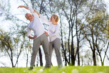 In shape. Positive active man doing an exercise while standing together with his trainer