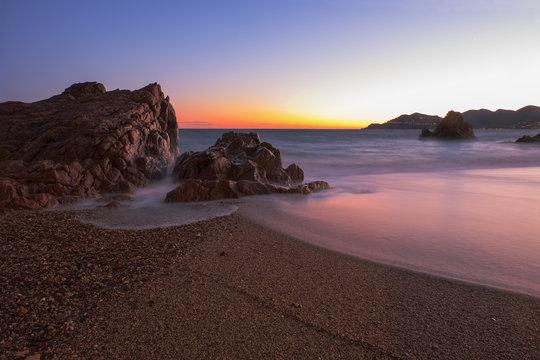 Une très belle plage et ses rochers rouges lors d'un incroyable couché de soleil dans le sud de la france