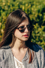 stylish hipster woman enjoying sunshine in sunny park. young girl with sunglasses posing in botanical garden in spring. space for text. relax and spa. springtime.